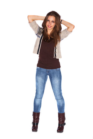 Standing beautiful young girl wearing heels and jeans is posing holding her hands behind her head. photo