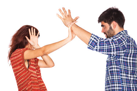 Young woman is covering her face while her violent husband wants to hit her with his hand - isolated on white photo