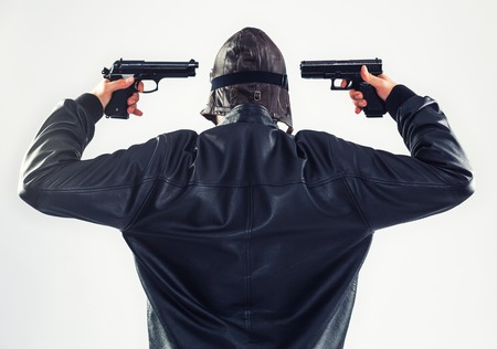 suicidal: Determined suicidal man is holding two guns pointed to his head - isolated on white