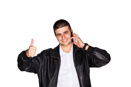 Young entrepreneur talking on the phone is gesturing thumbs-up - isolated on white photo