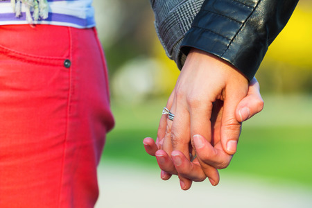 Closeup of a women couple holding hands together photo