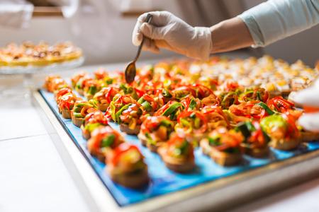 charolas: Chef está utilizando guantes para agregar el aderezo final sobre deliciosos canapés