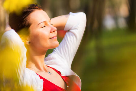 beatitude: Portrait of a young beautiful woman with eyes closed smiling in a sunny spring day Stock Photo