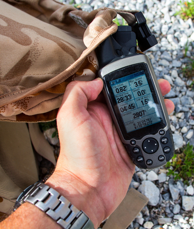 altimeter: A man on a mountain looking at a professional altimeter.