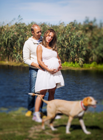 A husband and his pregnant wife holding each other on a lake, with their dog
