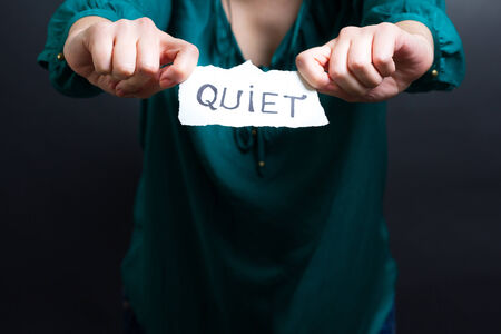 Image of hands holding a QUIET note photo