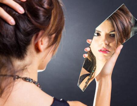 mirror image: Beautiful brunette watching herself in the mirror