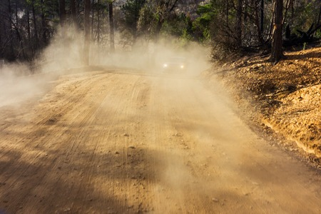The image of a off road car driving through a mountain dusty road