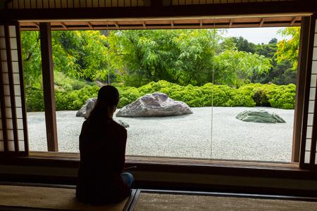 Woman looking through a window at a Japanese Zen Rock Garden. Editorial