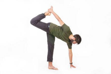 barefoot man: Portrait of a bearded barefoot man doing stretching exercises  - isolated on white.