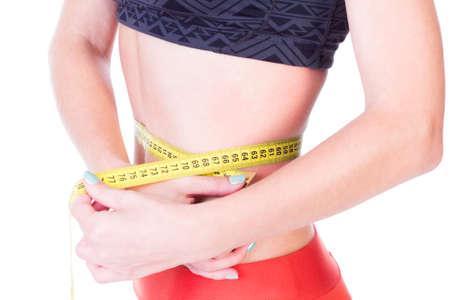 cintura perfecta: Perfecto medida de la cintura que muestra la p�rdida de peso con un cent�metro - aislado en blanco. Foto de archivo
