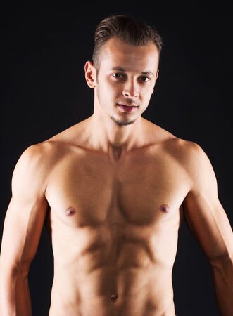 definite: Closeup of a young man with a perfect definite abdomen - isolated on black. Stock Photo