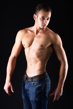 definite: Man with perfect definite muscles - isolated on black. Stock Photo