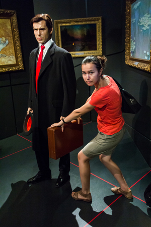 pierce: Los Angeles, CA, USA - 6th July 2013: Madame Tussauds Hollywood figures - Tourist stealing from James Bond (Pierce Brosnan)