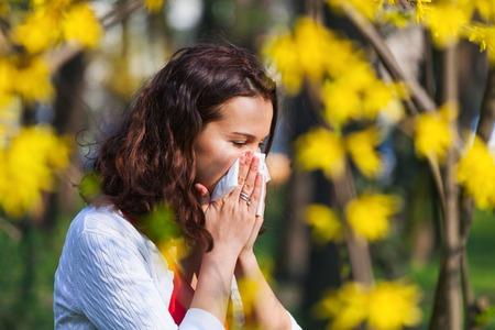 estornudo: Mujer joven que sopla su nariz mientras se est� en la naturaleza Foto de archivo