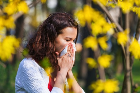 with pollen: Young woman blowing her nose while being in the nature Stock Photo