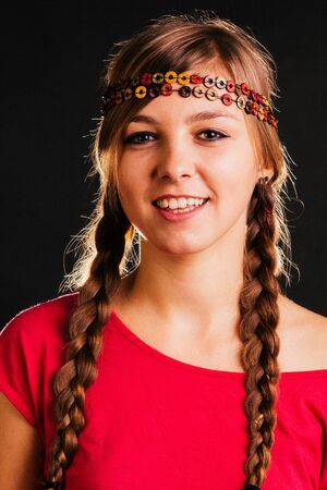 braids: Blonde young woman with long braids - isolated on black.