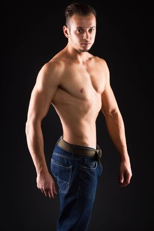 definite: Pose of young man with a perfect body - isolated on black.