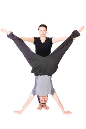 spreaded: Image of a woman holding a mans legs in gymnastics - isolated on white. Stock Photo