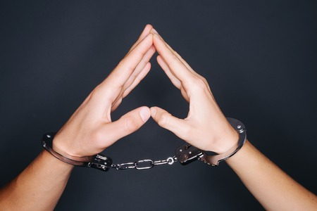handcuffed hands: Handcuffed man raising hands in air on black background and creating a heart shape. Stock Photo