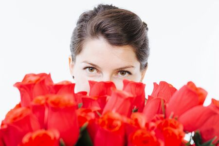 woman hiding: Woman hiding her face behind red roses - isolated on white