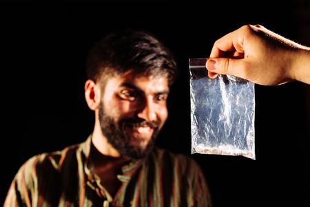 drug dealer: Drug dealer giving to an addict a packet of heroin or cocaine