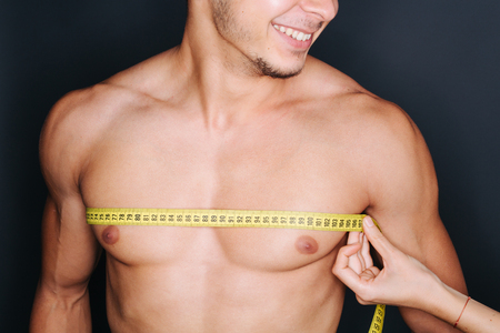 pecs: Muscular shirtless young man measuring chest and pecs with tape measure
