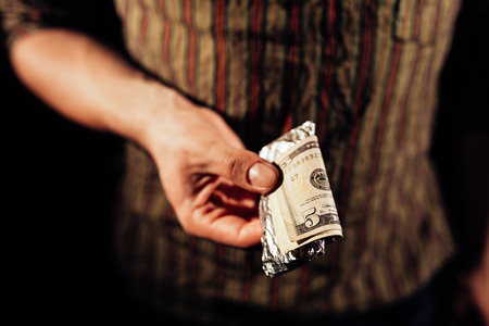 drug dealers: Drug dealers hand holding a package of cocaine with money on it