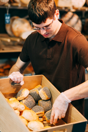 arranging: Salesman arranging different types of buns in the breadbasket