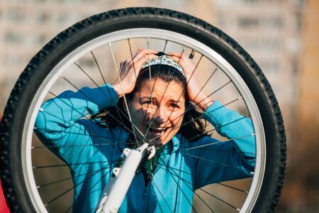 exasperation: Young woman with headache is trying to fix bike problem Stock Photo