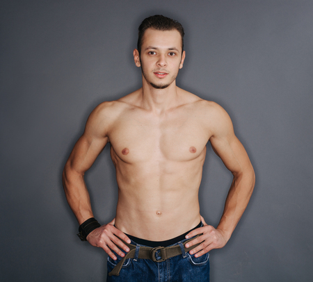 pecs: Young body art athlete with well trained pecs and abs  and blue jeans.