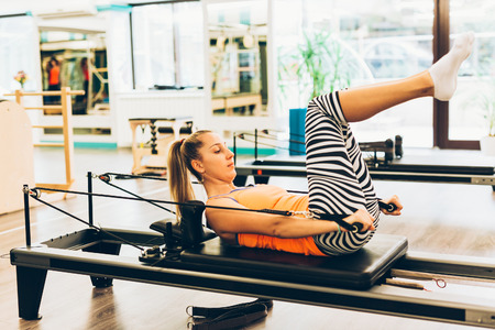 reformer: Young woman working out on a pilates reformer