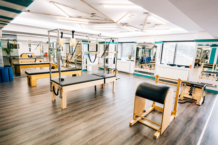 reformer: Room full of pilates equipment: exochairs, ladder barrel, reformer, cadillac and trapeze table Stock Photo