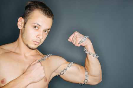 tense: Closeup of a young man with chains around tense biceps