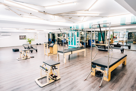trapeze: A gym full of pilates equipment: exochairs, ladder barrel, reformer, cadillac, trapeze table and other.