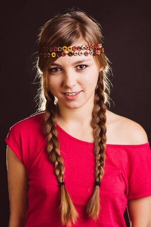 chic woman: Beautiful blond woman with braids and chic headband posing at studio - isolated on black. Stock Photo