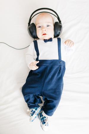 Elegant baby boy wearing headphones and lying in bed Stock Photo