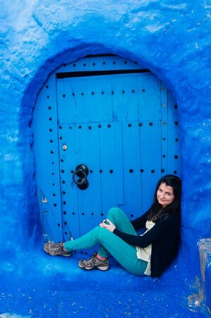 Tourist relaxing next to a wood door in Chefchaouen - the blue city of Morocco