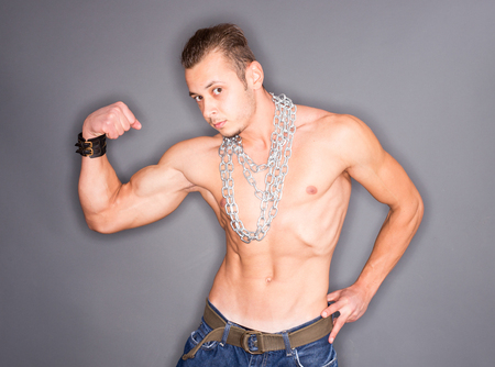 tense: Closeup of a shirtless muscular man posing with chains around his neck and showing his tense biceps