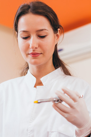 anesthetize: Closeup of female dentist holding a syringe and being ready to anesthetize