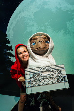 et: Los Angeles, CA, USA - July 6, 2013: Female tourist flying to the moon with E.T. science fiction character in Madame Tussauds Hollywood exhibition. Editorial
