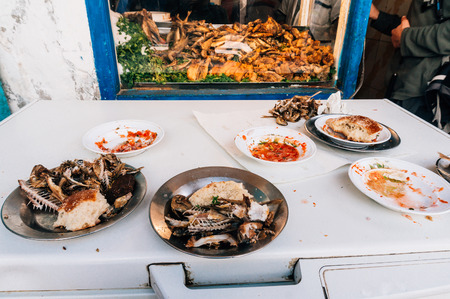 leftovers: Marrakesh, Morocco - February 6, 2015: Fish leftovers after delicious meal in a small local food shop from Moroccan harbor