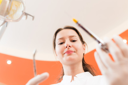 scrutinize: Closeup of a female dentist holding a syringe and a probe in hands. Patients view