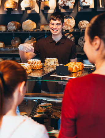 shopkeeper: Bakery shopkeeper gives pastry products to customers Stock Photo