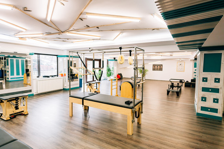 trapeze: Pilates room with several devices like trapeze table, reformers, chairs etc