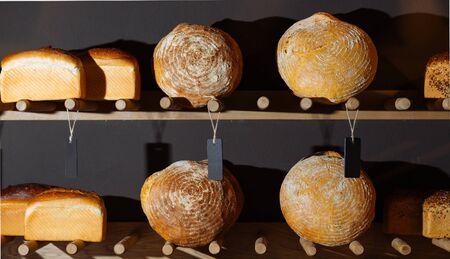 unsliced: Closeup of types of fresh bread on shelf in bakery