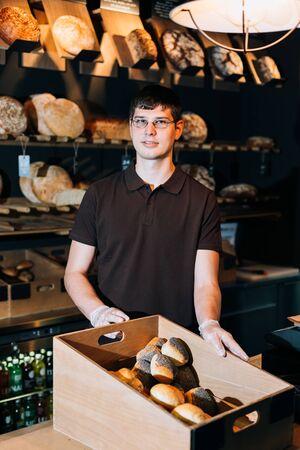 breadbasket: Shopkeeper presents a breadbasket to customer in a bakery Stock Photo