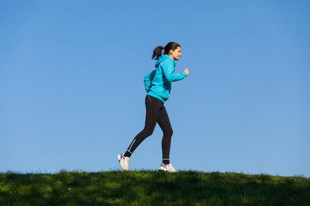feeling good: Smiling female runner feeling good training in the park