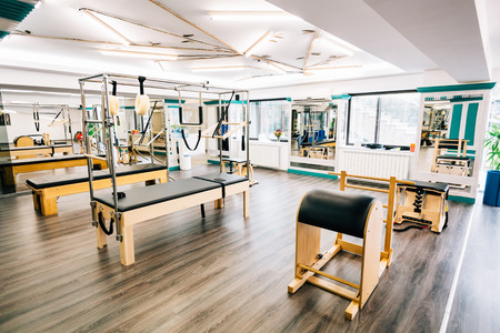 trapeze: Trapeze table, reformer, ladder barrel in a pilates room