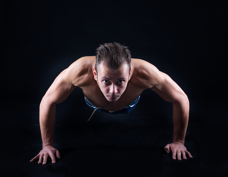 push ups: Muscular man doing push ups and looking to camera